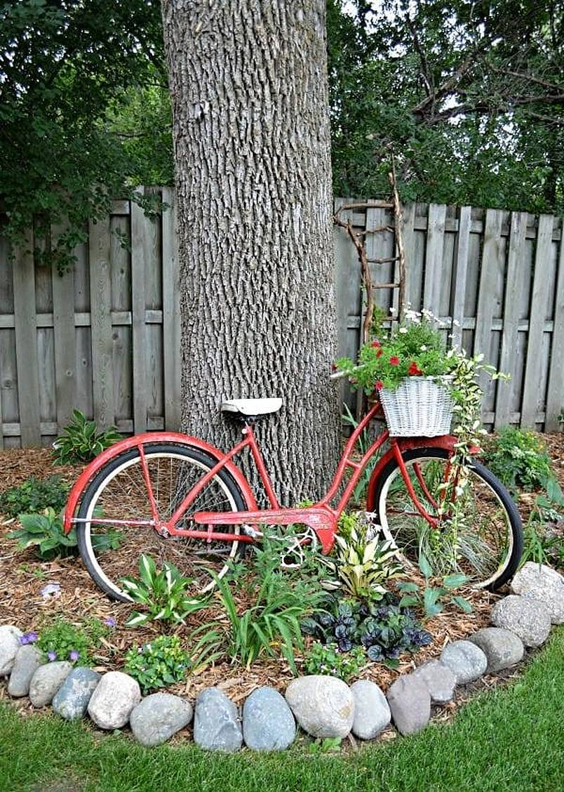 Old red bike leaning against a tree