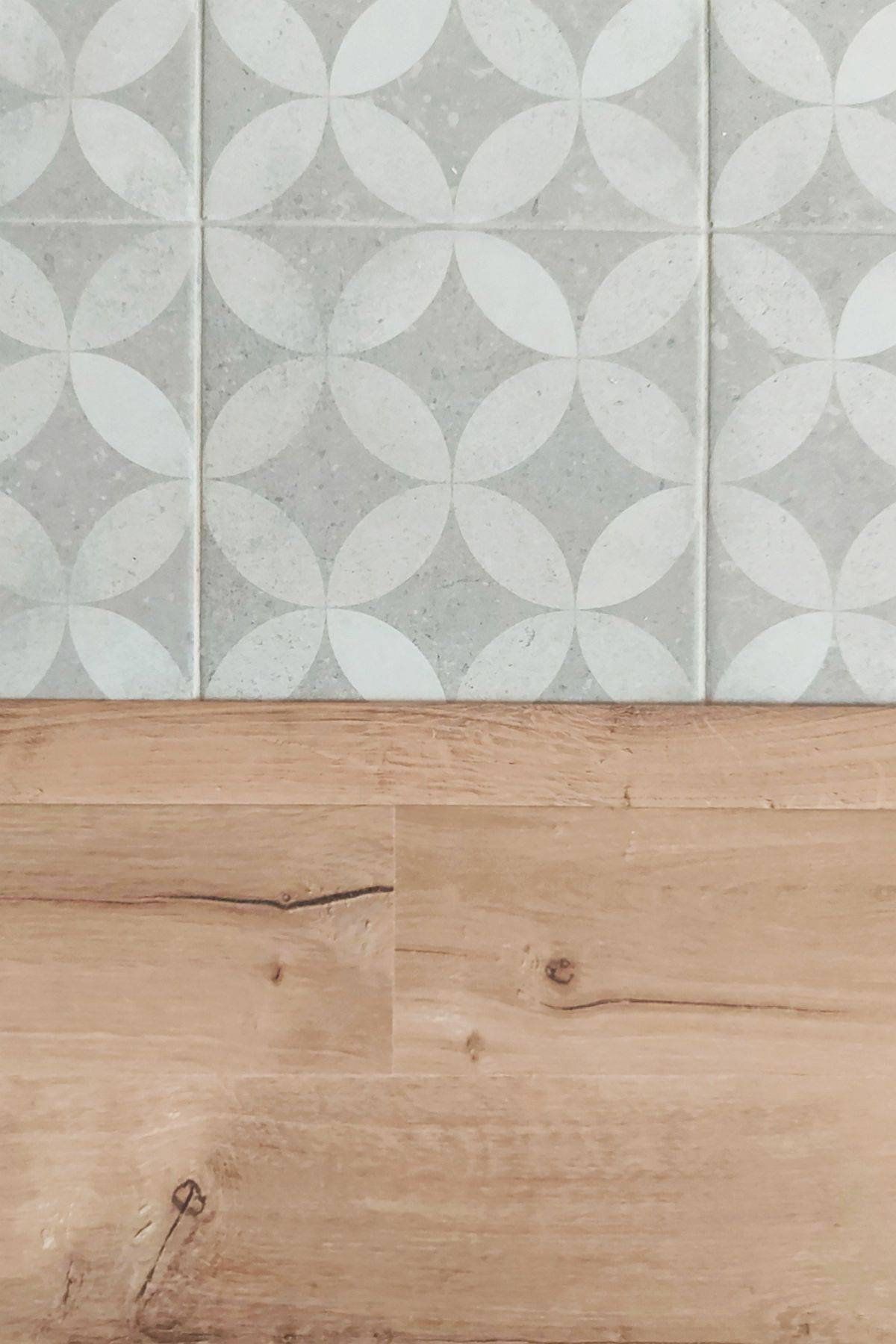 Patterned-tile floor of the kitchen next to the wooden floor of the living room