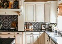 Patterned tiles in kitchen wall with white cupboards