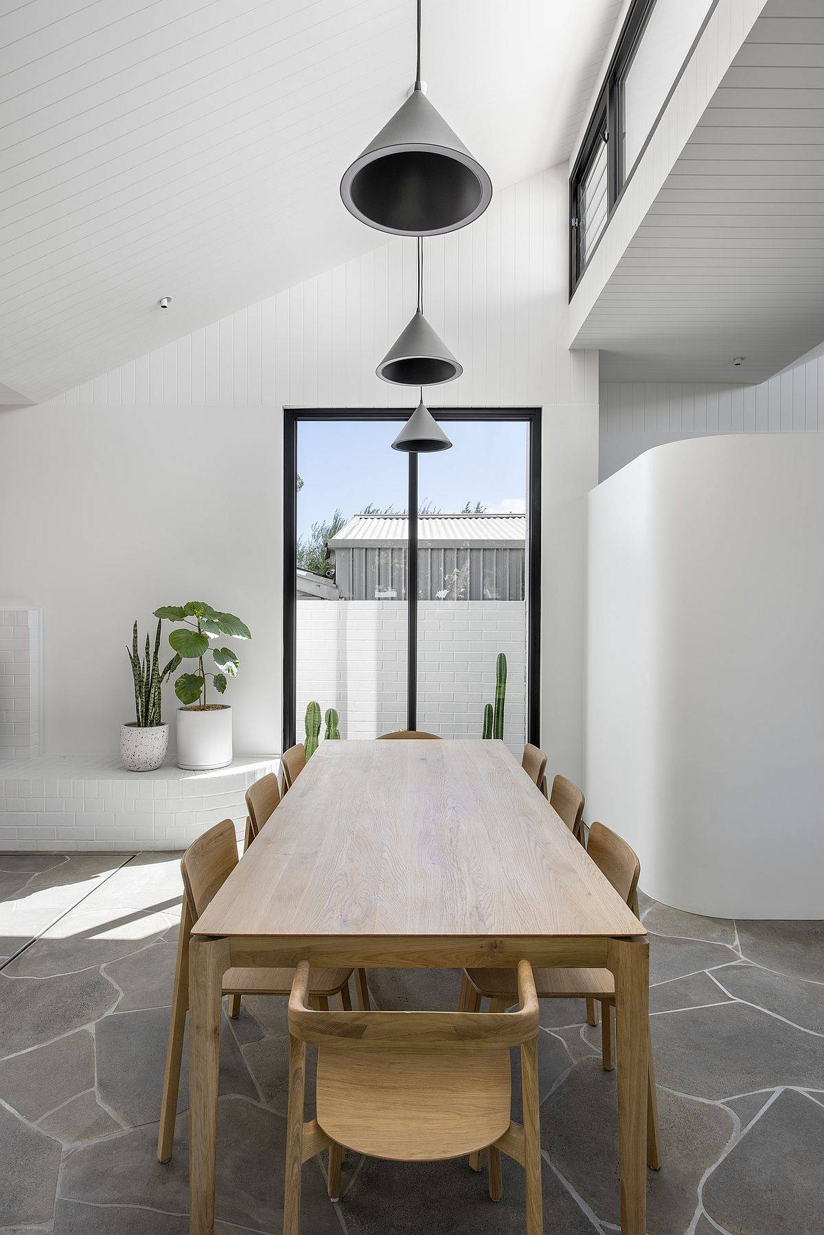 Sloped ceiling and black pendant lights turn this dining area into a special space