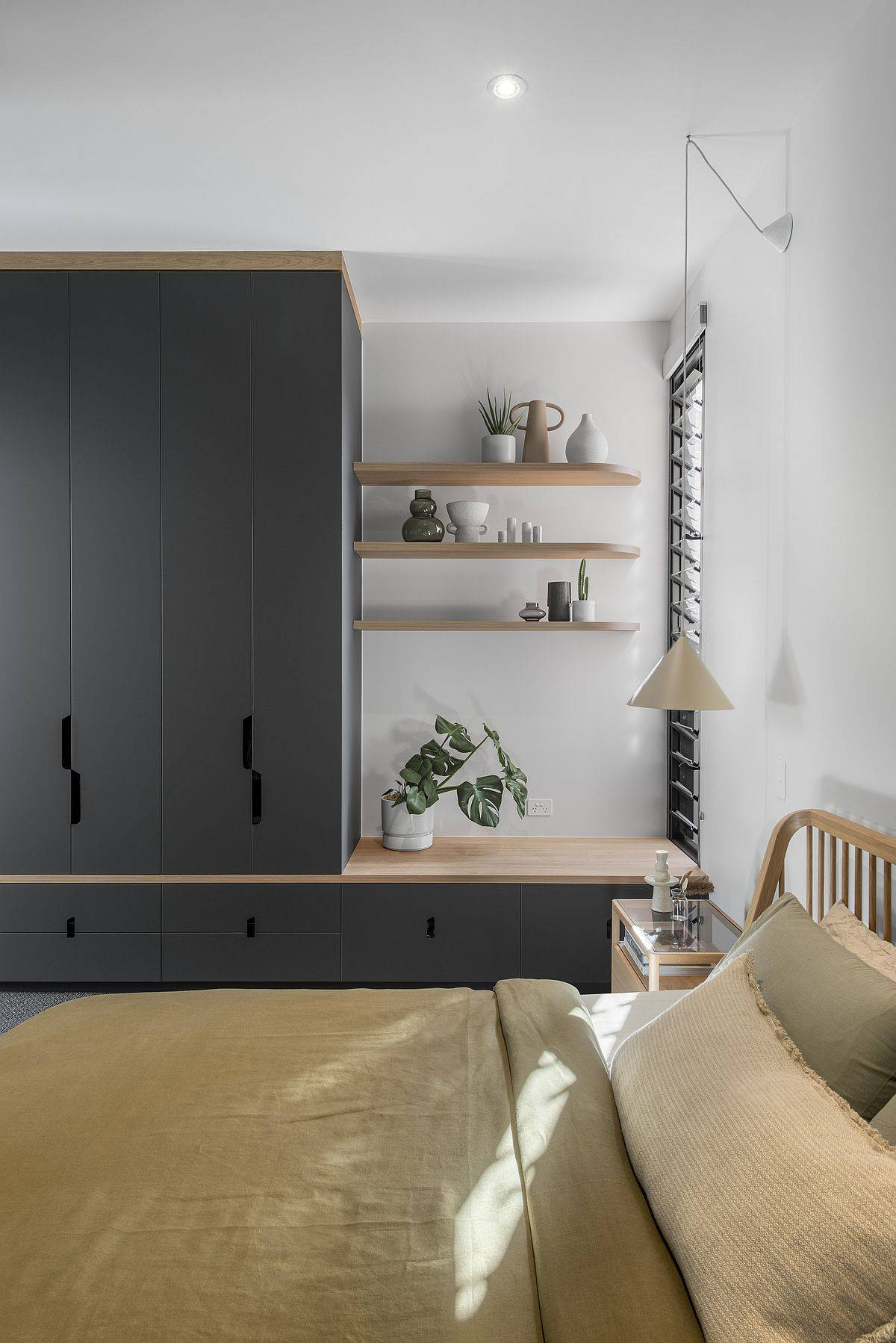 Small and space-savvy modern bedroom in white with dark gray cabinets