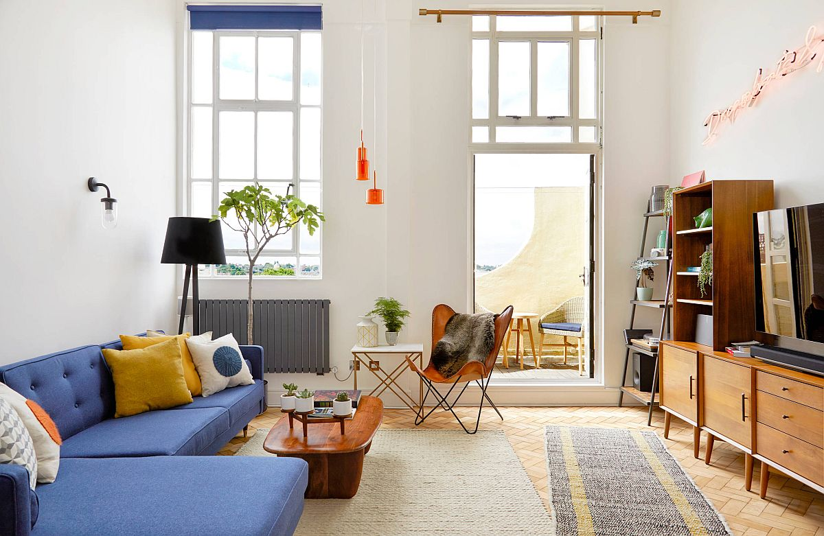 Smart midcentury modern living room with blue couch and accent pillow in yellow