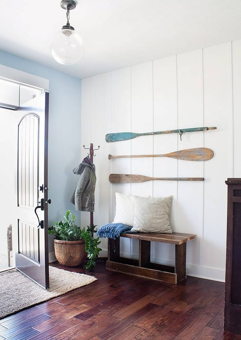 Three paddles on white wall in entryway with bench and cushions