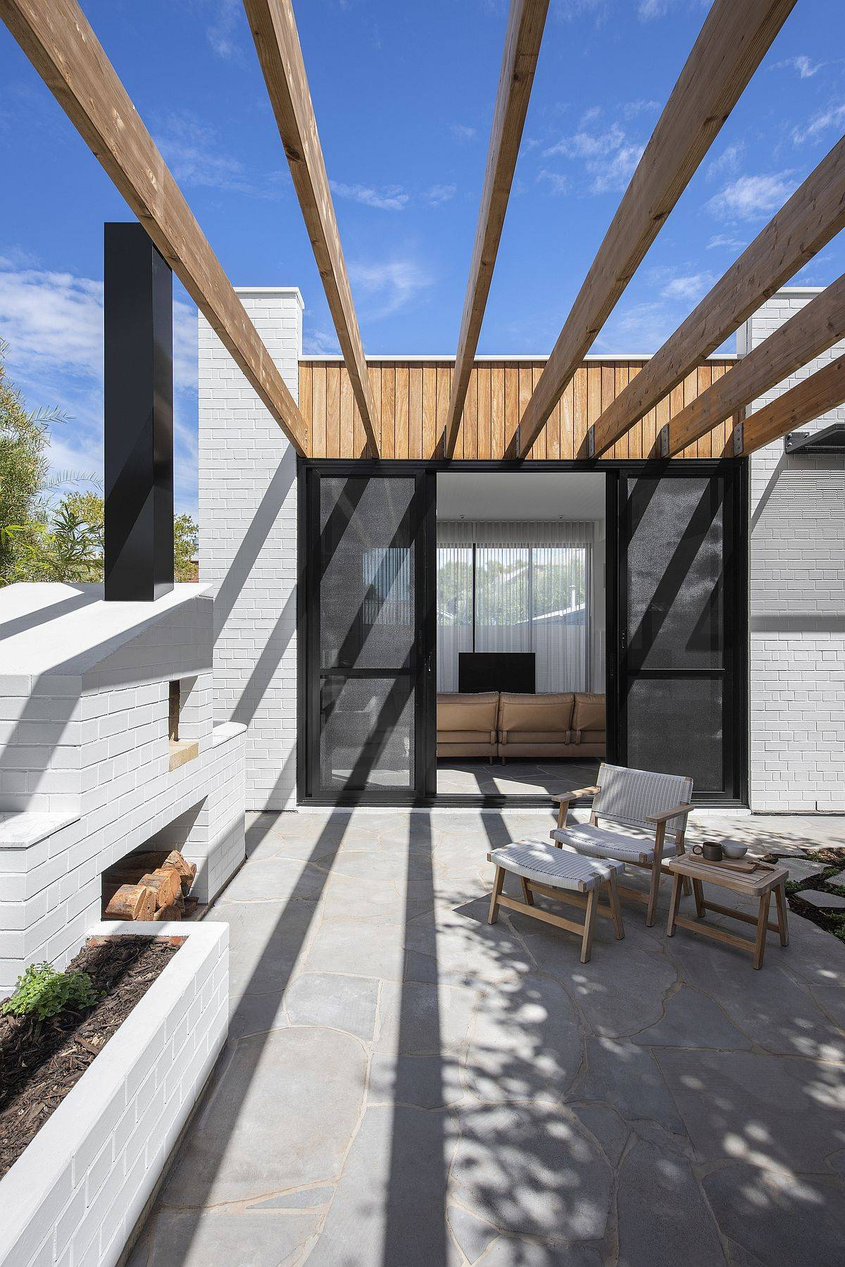 Timber beams offer shade for the outdoor sitting area
