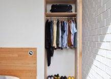 Tiny-and-open-mens-closet-design-in-wood-is-neatlly-tucked-into-the-space-next-to-the-bed-93770-217x155