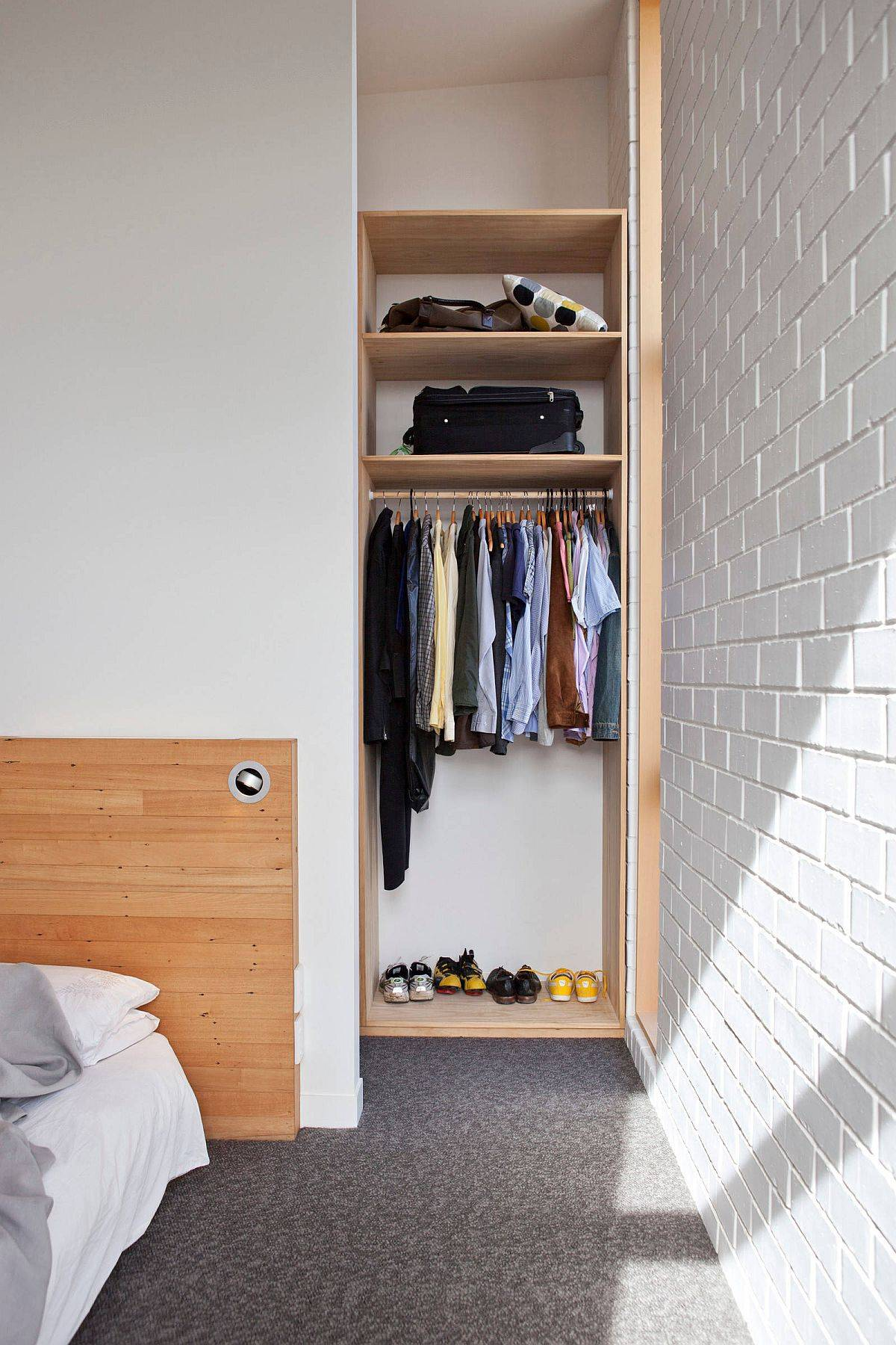 Tiny and open men's closet design in wood is neatlly tucked into the space next to the bed
