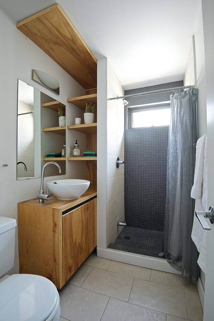 Tiny bathroom with space-savvy design and a wooden vanity