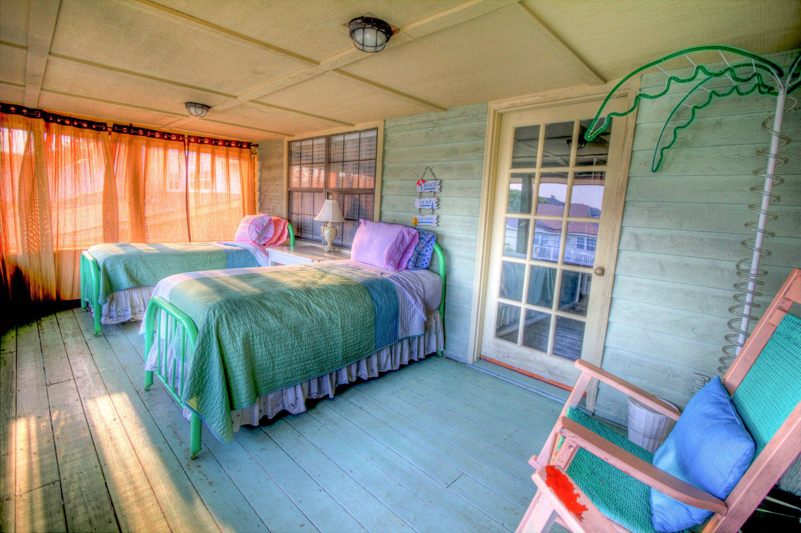 Two beds in spacious bedroom with orange sheer curtain and palm tree stand at the side