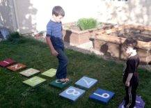 Two boys playing on hopscotch tiles
