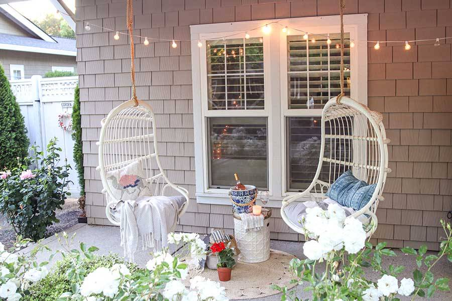 Two hanging white chairs in front of window