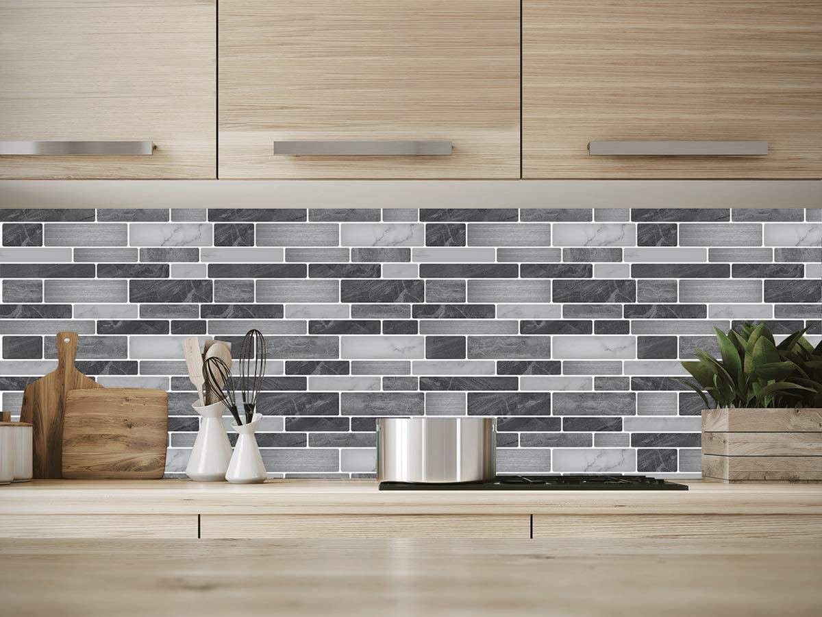 Vinyl decorative tiles in different grey hues in kitchen wall