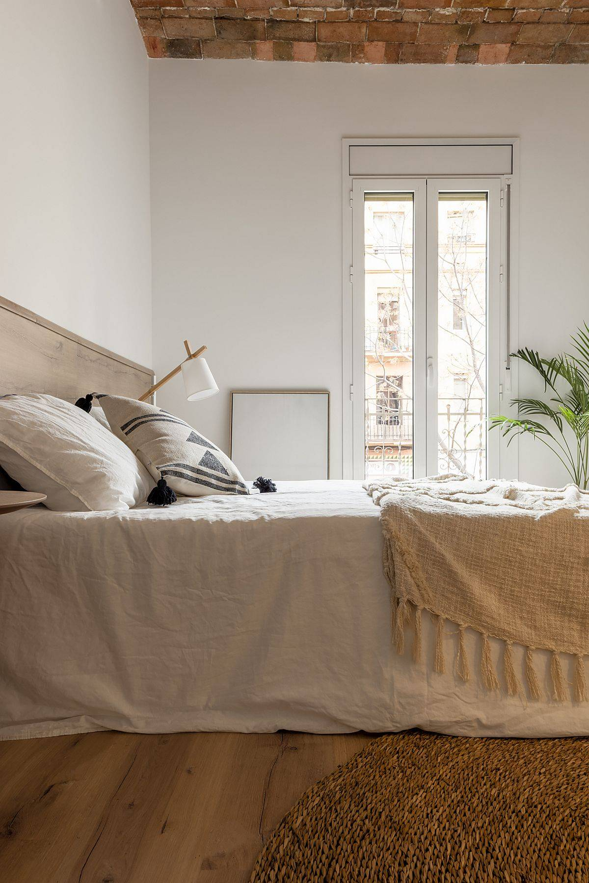 White and wood bedroom of the Barcelona home with organic finishes