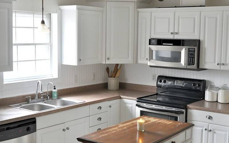 White cabinetry in kitchen with one candle on counter