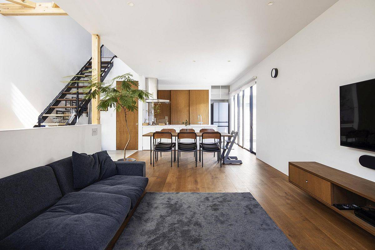 Wooden floor delineates the living room and dining area from other spaces of the house