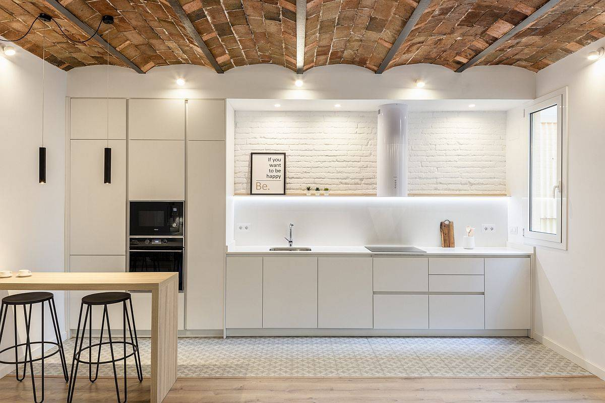 White and wood kitchen with lovelu ceiling tiles and an exposed brick wall section