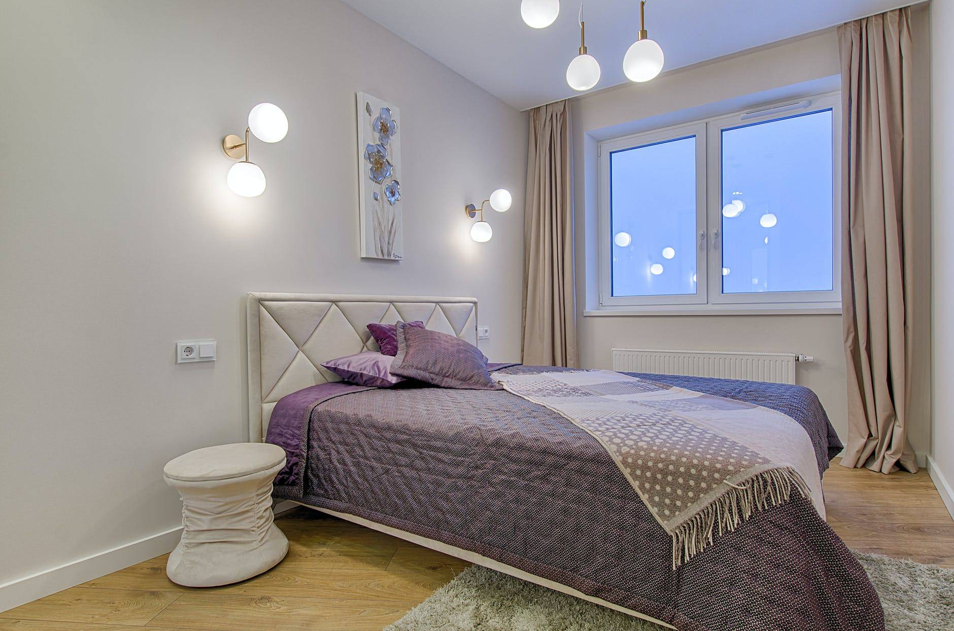 Bed with purple sheets and cushions