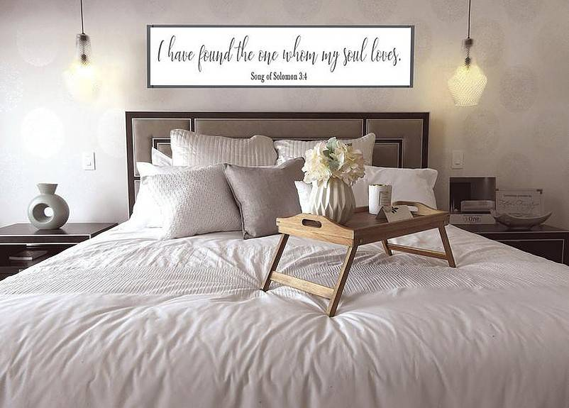 Bedroom slogan sign on the wall above bed