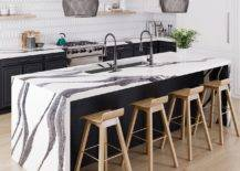 Black and white kitchen counter with sink and wooden chairs