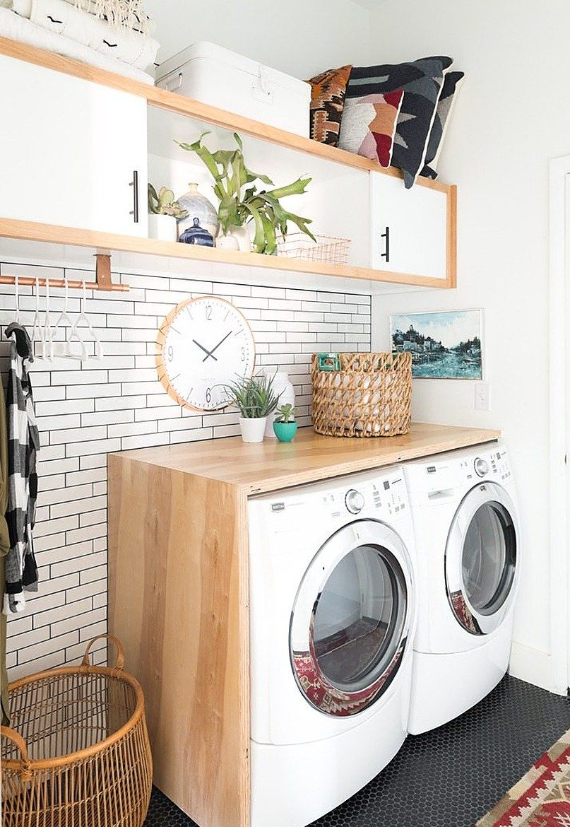 Brown basket and wall clock on top of washer and dryer