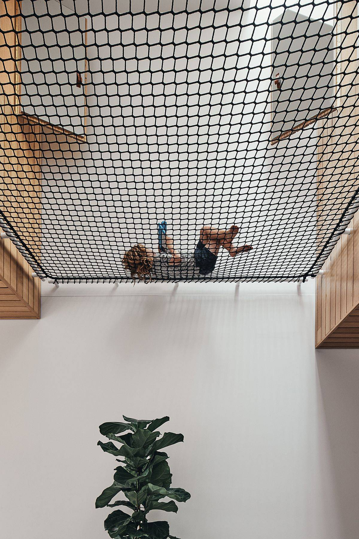 Central void of the home with a net on the upper level that helps everyone rest and relax