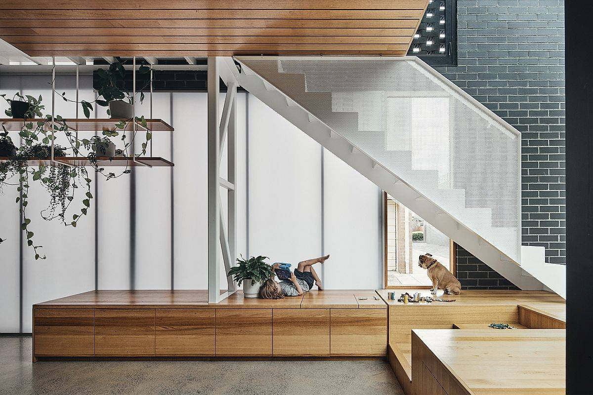 Custom wooden platform under the staircase with wooden storage built-in boxes