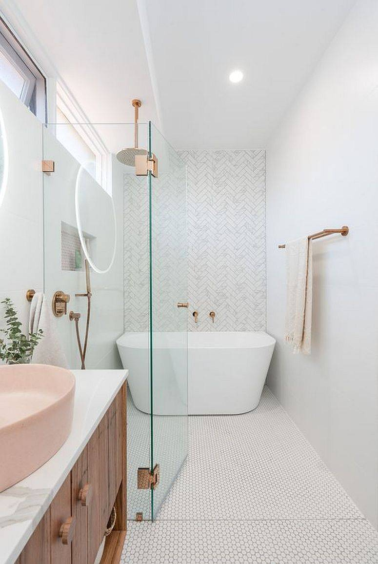 Fabulous white bathroom with herringbone pattern backdrop and penny tile floor along with light pastel pink sink