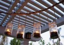 Four mason jars hanging with tea lights hanging from pergola