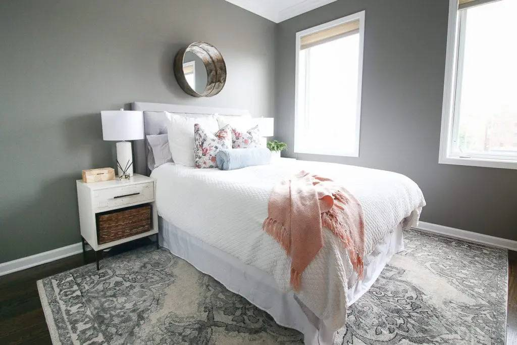 Fringed shawl on top of white bed