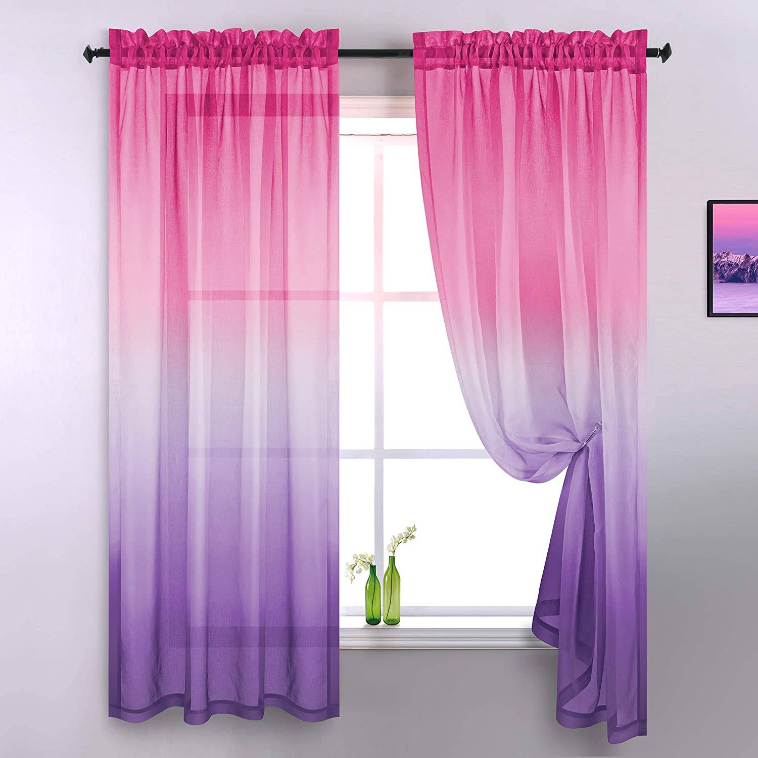 Green bottles with flowers on window having pink and purple curtain
