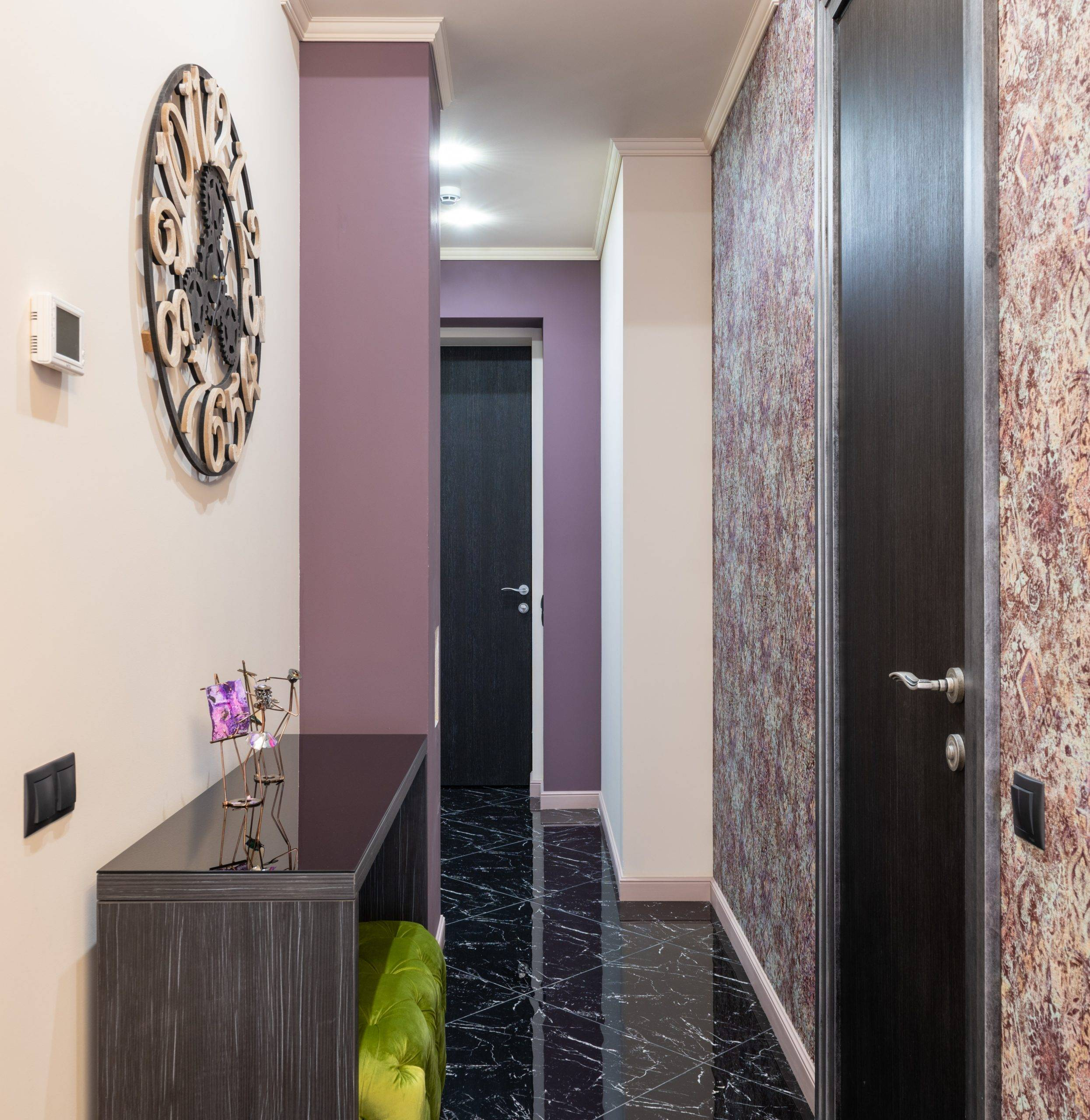 Hallway with lavender walls and huge round clock