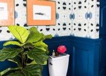 Huge plant beside toilet in blue-walled bathroom