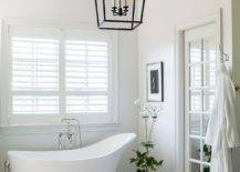 Indoor-plant-and-the-lighting-fixture-bring-a-bit-of-contrast-to-the-white-bathroom-with-marble-floor-55110-217x155