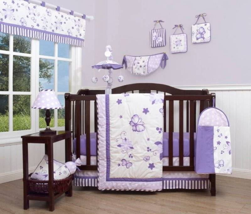 Lavender nursery room with dark brown crib and side table