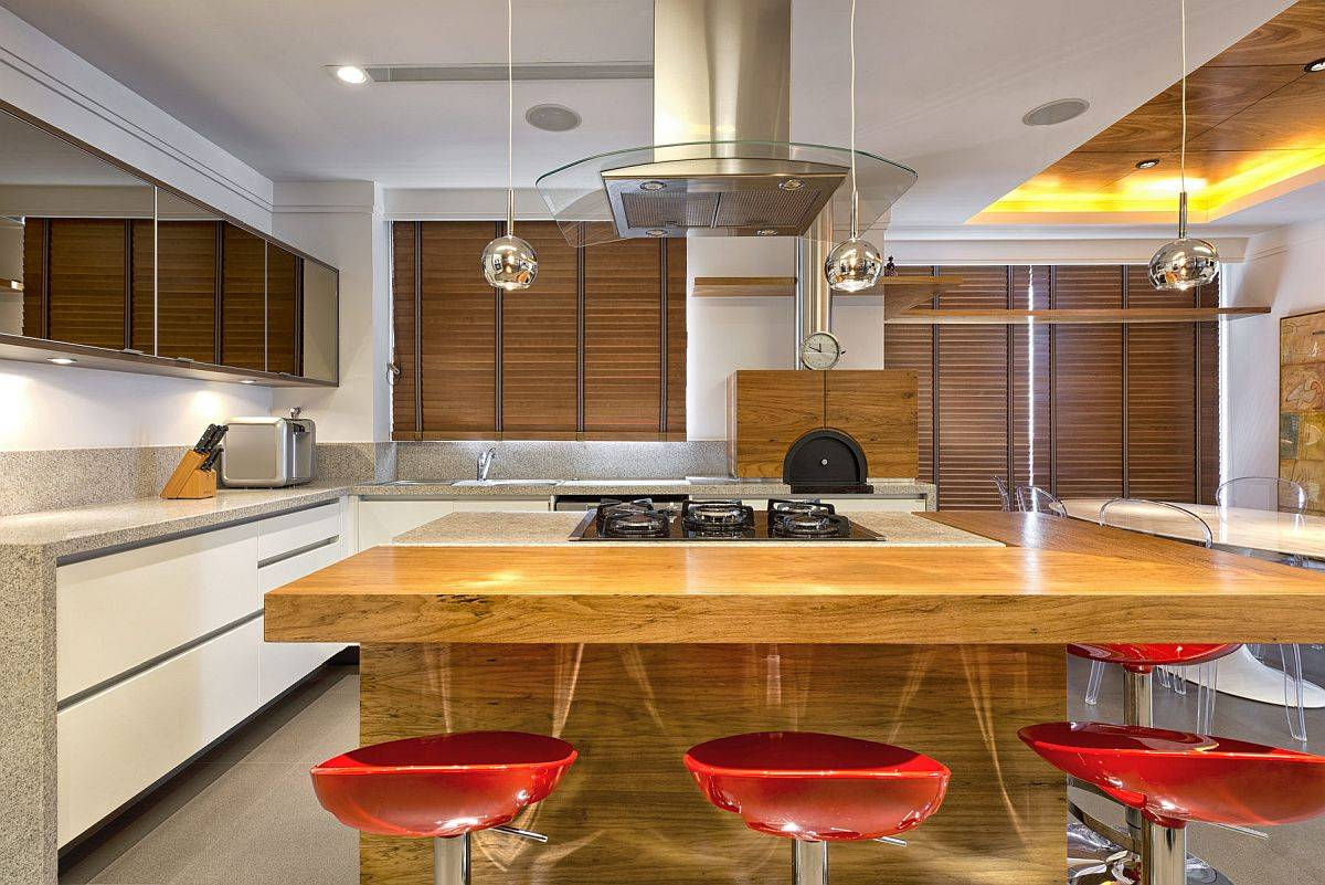 Moder-kitchen-in-white-with-stone-countertops-and-wooden-counters-along-bright-red-bar-stools-97438