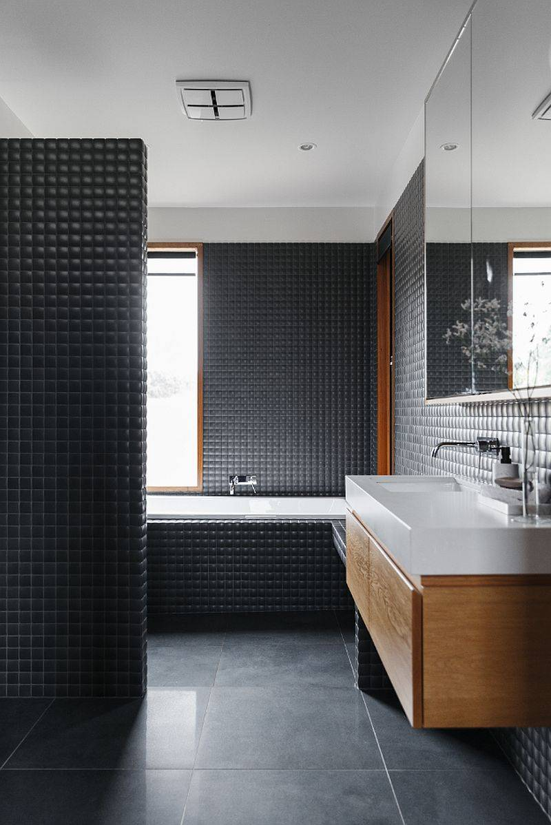 Modern bathroom in dark gray with floating wooden vanity and a white countertop and sink