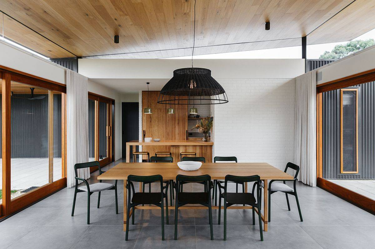 Modern dining room of the Aussie home with gray floor, sliding glass doors and wooden table