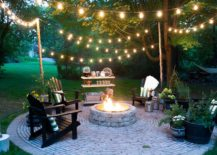 Outdoor fire put surrounded by black chairs, plants and dangling lights