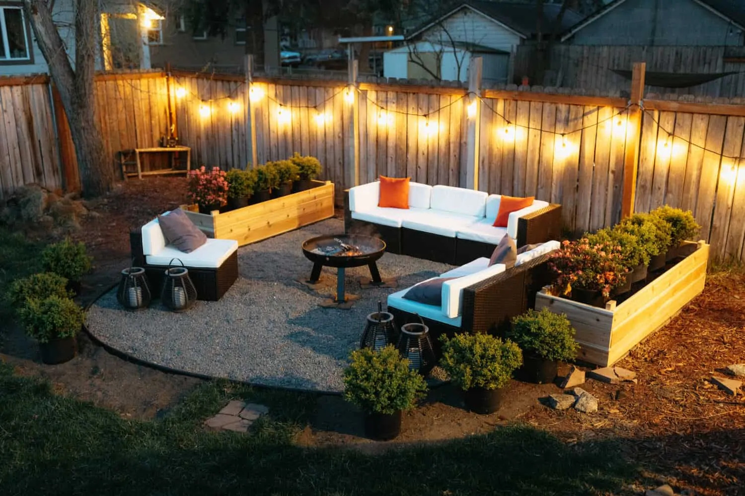 Outdoor firepit surrounded by white sofa with cushions and planters