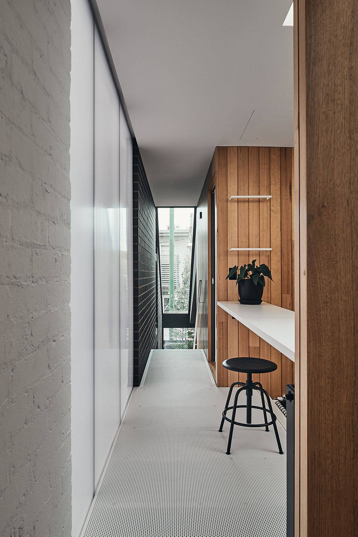 Painted brick walls, polycarbonate panels and woodsy finishes combined inside the smart Aussie home