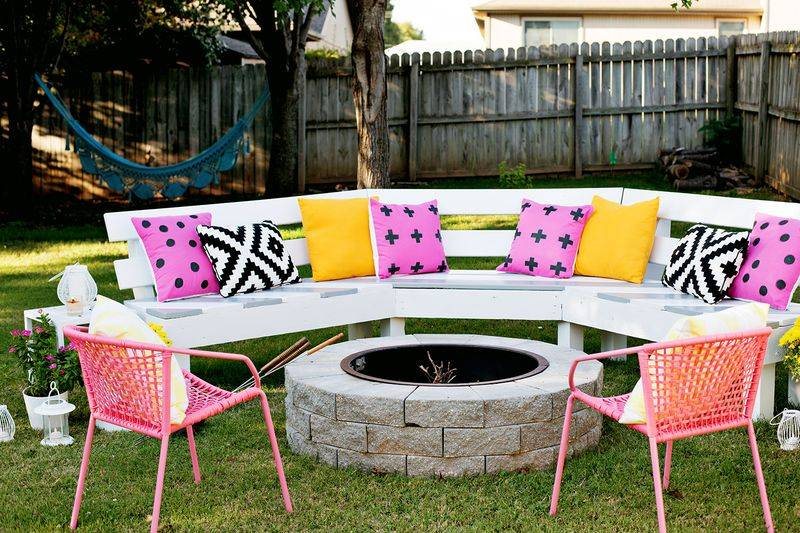 Pink and yellow cushions on long outdoor bench