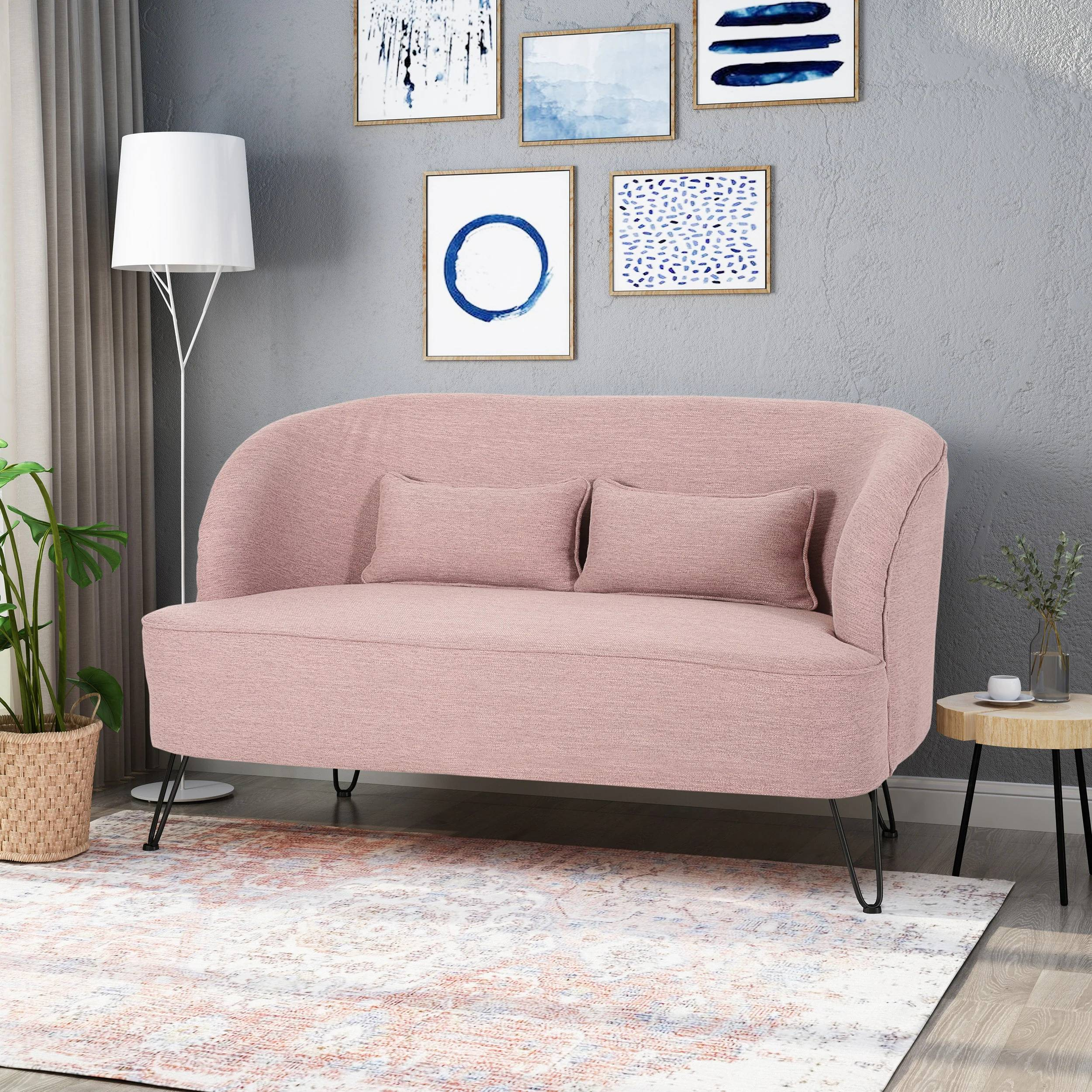 Pink sofa beside tall white lampshade