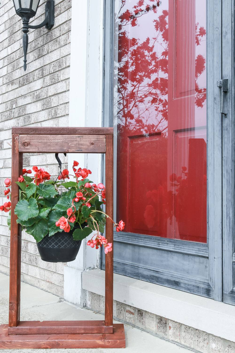 Red flowers hanging on a wood stand