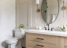 Round bathroom mirror in the middle of wall lamps