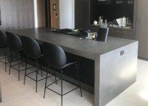 Sleek black kitchen counter with black accent chairs