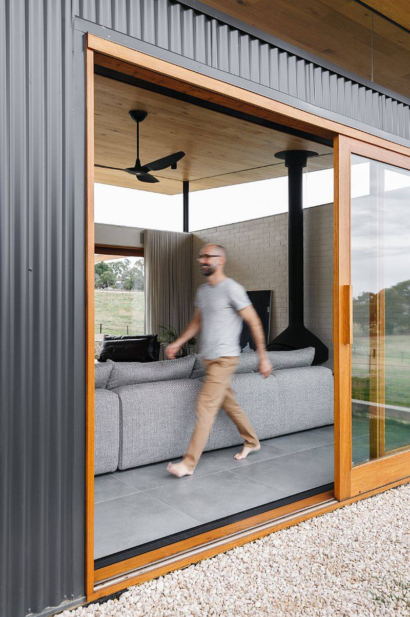 Sliding doors with wooden frame connect the new living room with the world outside