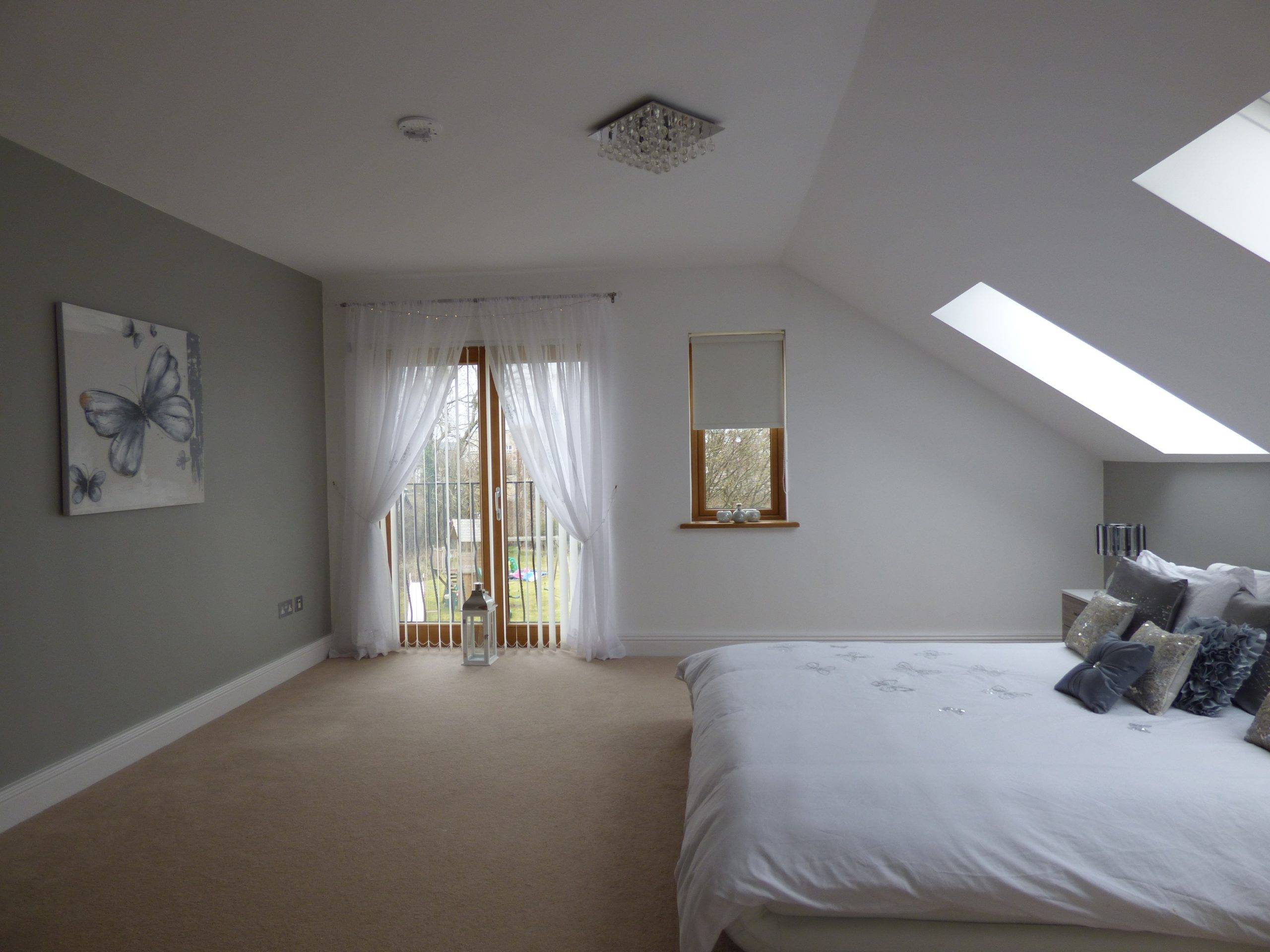 Spacious grey bedroom with large bed