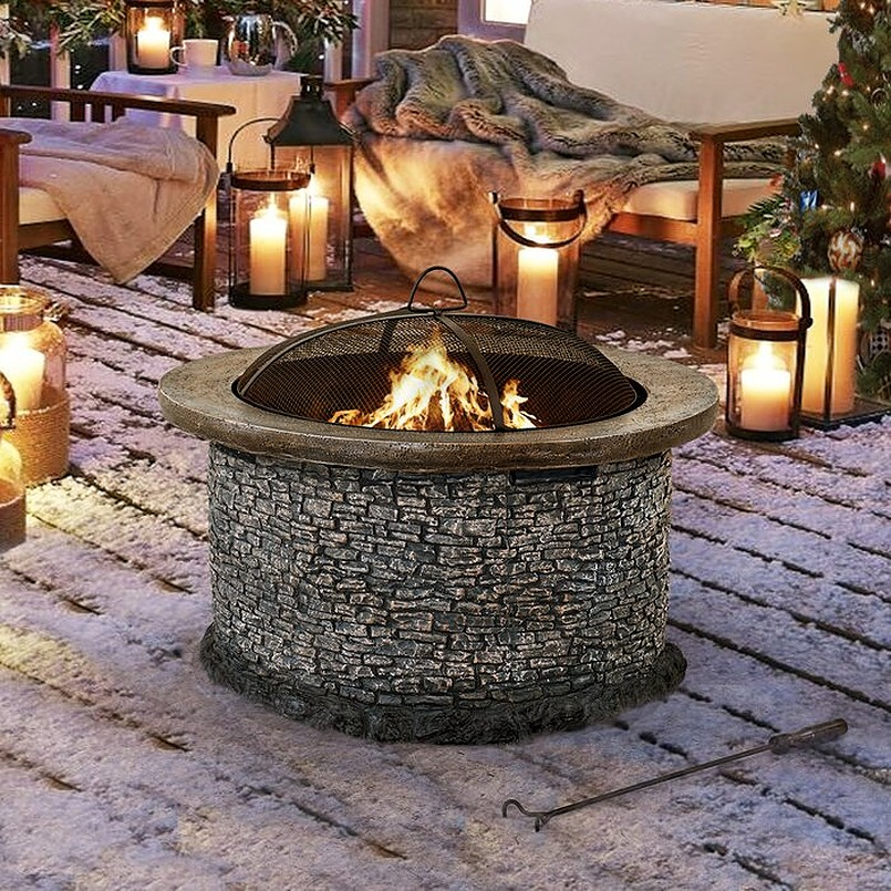 Stone fire pit with sofa bed and blanket