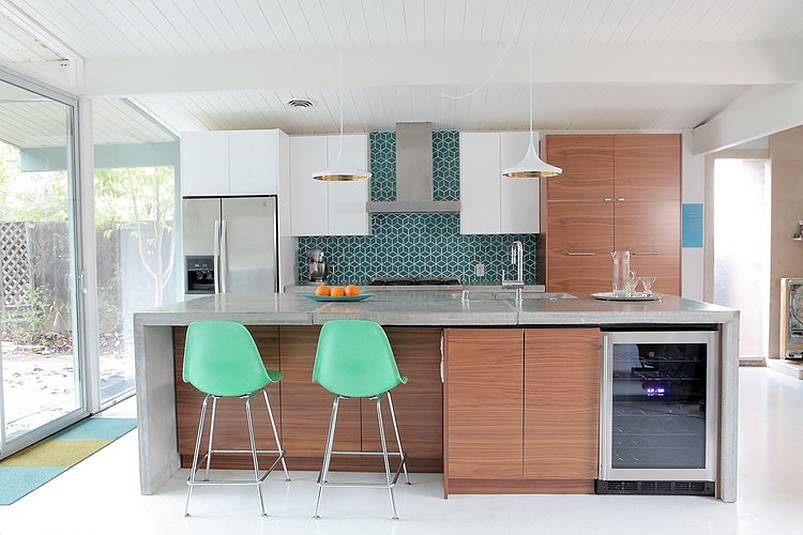 Three oranges on countertop with two mint green chairs