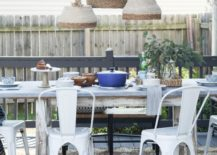 Three pendant lights made from baskets hanging above table on outside deck