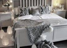 White and grey bed with string lights and pictures at the head
